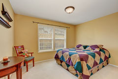 Kids bedroom with colorful bed  and pastel yellow walls. Royalty Free Stock Images