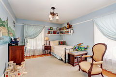 Kids bedroom interior in blue tones with cherry wooden furniture and nice curtains. Stock Photography