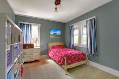 Kids bedroom with red bed and grey walls. Royalty Free Stock Photo