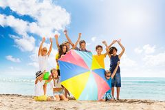 Kids behind huge beach umbrella lift hands Royalty Free Stock Photo