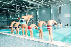 Kids bents over and ready to jump into pool. With clean blue water. View from back. Children learn to swim and dive. Modern sports center on background Stock Photo