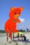 Kids and big orange bear kite Royalty Free Stock Photo