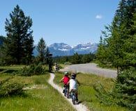 Kids biking outdoors royalty free stock photos