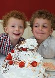 Kids and Birthday Cake. Two boys with a huge decorated birthday cake (8 and 3 years old Royalty Free Stock Image