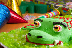 Kids birthday cake and decorations. Closeup of kids birthday crocodile cake with party decorations and presents Stock Image