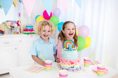 Kids birthday party with cake. Kids birthday party with colorful pastel decoration and rainbow cake. Girl and boy with sweets, candy and fruit. Balloons and stock images