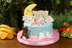 Kids birthday party cake - sky consept. Big birthday cake decorated with sky, clouds, stars, moon, rainbow, baby and bear Stock Photo