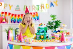 Child birthday party. Kids blow candle on cake. Kids birthday party. Child blowing candles on cake and opening presents on jungle theme celebration. Sweets and stock image