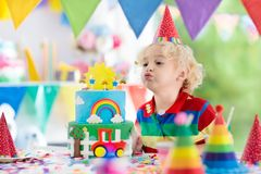 Kids birthday party. Child blowing out cake candle. Kids birthday party. Child blowing out candles on colorful cake. Decorated home with rainbow flag banners stock image