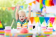 Kids birthday party. Child blowing out cake candle. Kids birthday party. Child blowing out candles on colorful cake. Decorated home with rainbow flag banners stock photos