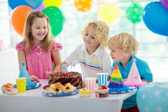 Kids birthday party. Child blowing out candles on colorful cake. Decorated home with rainbow flag banners, balloons. Farm animals royalty free stock photo