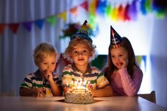 Kids birthday party. Children blow cake candles. Royalty Free Stock Photos