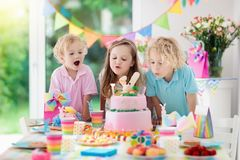 Kids birthday party. Children blow cake candles. Kids birthday party. Children blow out candles on pink bunny cake. Pastel rainbow decoration and table setting Royalty Free Stock Photo