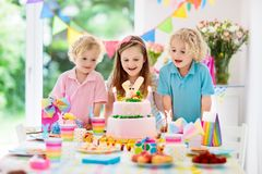 Kids birthday party. Children blow cake candles. Kids birthday party. Children blow out candles on pink bunny cake. Pastel rainbow decoration and table setting Stock Photography