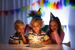 Kids birthday party. Children blow cake candles. Stock Photography