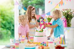 Kids birthday party. Children blow cake candles. Kids birthday party. Children blow out candles on pink bunny cake. Pastel rainbow decoration and table setting Stock Photo