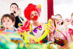 Kids birthday party with clown and lot of noise. Children celebrating birthday party with noisemakers while a clown is visiting entertaining the kids stock image