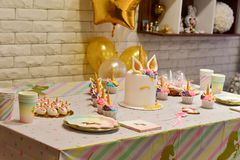 Unicorn party cupcake and cake. Kids birthday party decoration and cake. Decorated table for child birthday celebration. Rainbow unicorn cupcake stock photography
