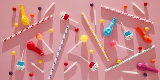 Kids birthday party decoration, pink background pattern. Colorful candies, bright balloon, festive candles, and paper straws stock image