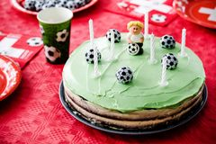Kids birthday party Football theme. Chocolate cake decorated lik. E football field with seven candles Stock Photo