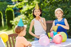Kids at birthday party. Kids celebrate together at birthday party with balloons in summer in garden stock photo