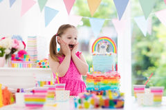 Kids birthday party. Little girl with cake. Kids birthday party with colorful pastel decoration and unicorn rainbow cake. Little girl with sweets, candy and Stock Image