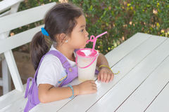 Kids black hair is drinking fruit smoothies. Kids black hair is drinking fruit smoothies on white table Royalty Free Stock Photos