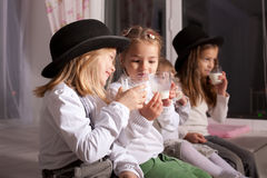 Kids in black hats drink milk. Royalty Free Stock Photos