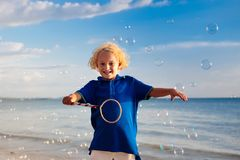 Kids blow bubble at beach. Child with bubbles. Kids blow bubbles at tropical beach. Child blowing soap bubble playing at sea. Family summer vacation with young stock image