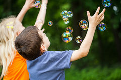 Kids blowing bubbles Stock Images