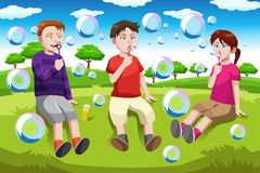 Kids blowing bubbles Stock Photo