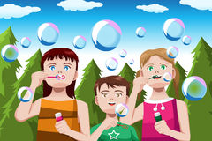 Kids blowing bubbles Royalty Free Stock Photos