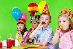 Kids Blowing Into Party Horns Stock Photo