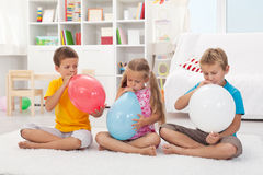 Kids blowing large balloons royalty free stock image