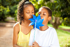 Kids blowing on a pinwheel. Two kids blowing on a pinwheel together Stock Photography