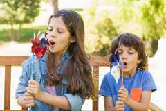 Kids blowing pinwheels on park bench Royalty Free Stock Photo