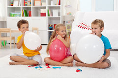 Kids blowing up balloons Royalty Free Stock Image