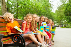 Kids with blue notebooks sit in row on bench Stock Photo