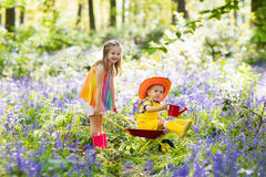 Kids with bluebell flowers, garden tools stock photos