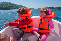 Kids in a boat. Kids floating in a boat in the middle of the river royalty free stock photography