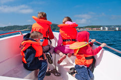 The kids in a boat. The picture of the kids sitting in a boat for a ride stock image