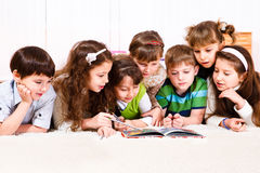 Kids with book. Kids crowd reading a book Royalty Free Stock Photography