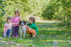 Kids - boy and girl - with dog outdoors Stock Photo