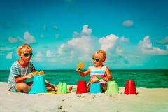 Kids- boy and girl play with toys on sand beach. Kids- boy and girl play with toys on tropical sand beach stock photo