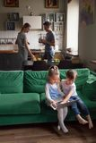Kids using laptop together while parents in the kitchen. Kids boy and girl using laptop together on sofa while parents preparing breakfast in the kitchen royalty free stock images