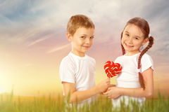 Kids, boy gives a little girl candy red lollipop in heart shape outdoor stock images