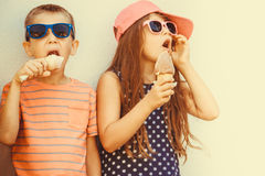 Kids boy and little girl eating ice cream. Kids eating gelato and soft serve ice cream. Boy and little girl in sunglasses enjoying summer holidays vacation stock images