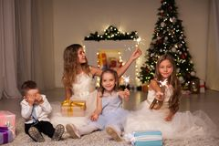 Children at Christmas sparklers new year gifts. Kids boy and three girls at Christmas sparklers new year gifts stock images