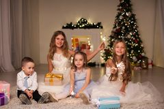 Children at Christmas sparklers new year gifts. Kids boy and three girls at Christmas sparklers new year gifts royalty free stock photos