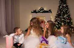 Children at Christmas sparklers new year gifts. Kids boy and three girls at Christmas sparklers new year gifts royalty free stock photography